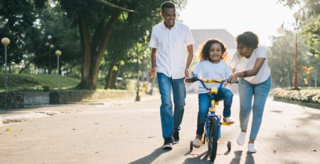 family with girl learning how to bicycle